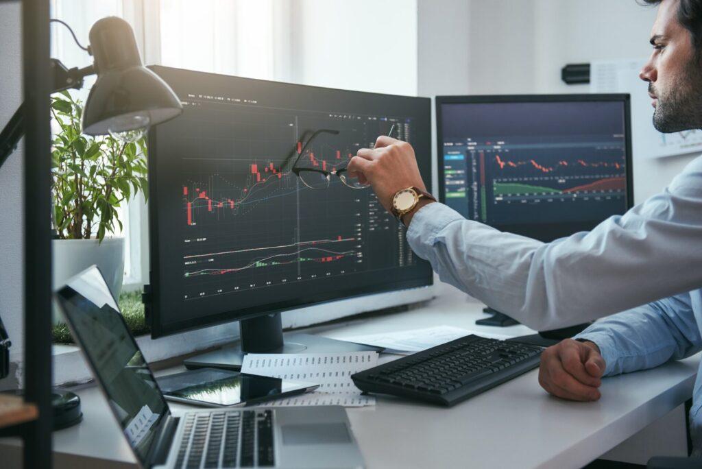 Rynek Forex. Młody trader wskazuje na wykresy na ekranie komputera i analizuje dane podczas pracy